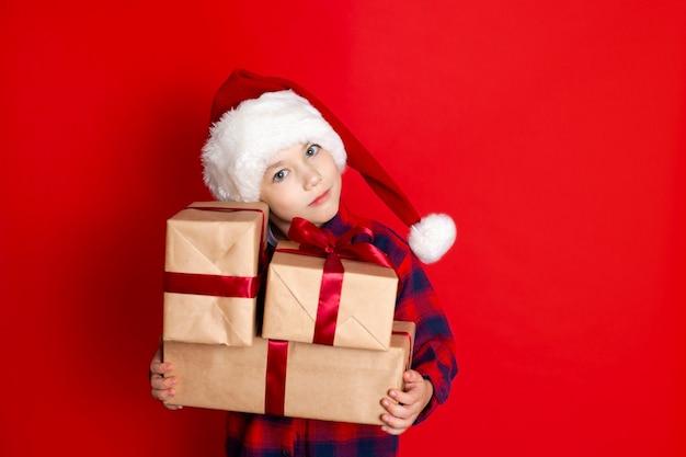 Boas festas e feliz natal. retrato de um menino em um boné com presentes nas mãos sobre um fundo vermelho. um lugar para texto. foto de alta qualidade
