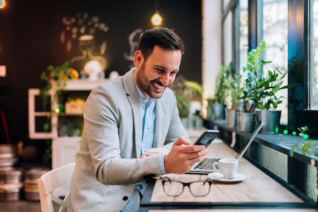 Boas notícias do colega. homem de negócios novo que guarda o smartphone no café.