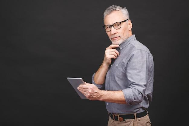 Boas notícias! empresário maduro bonito em roupas casuais inteligentes e óculos está usando um tablet digital e sorrindo,