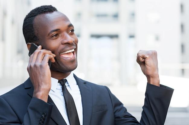 Boas notícias! jovem africano feliz em trajes formais falando ao telefone e expressando positividade ao ar livre