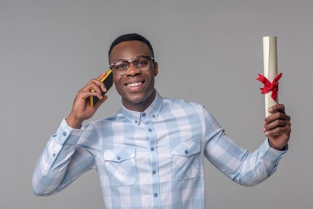 Boas noticias. jovem feliz de pele escura de óculos com papéis enrolados nas mãos falando em smartphone