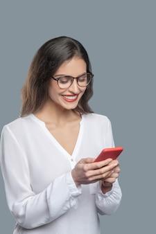 Boas notícias. mulher bonita envolvida alegre de óculos olhando atentamente para o smartphone nas mãos