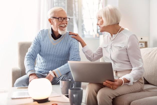 Boas notícias. mulher idosa alegre segurando um laptop e rindo junto com o marido enquanto discutia as notícias recentes, depois de lê-las online