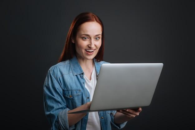 Boas notícias. mulher otimista e idiota checando suas cartas e descobrindo novidades enquanto usa seu laptop