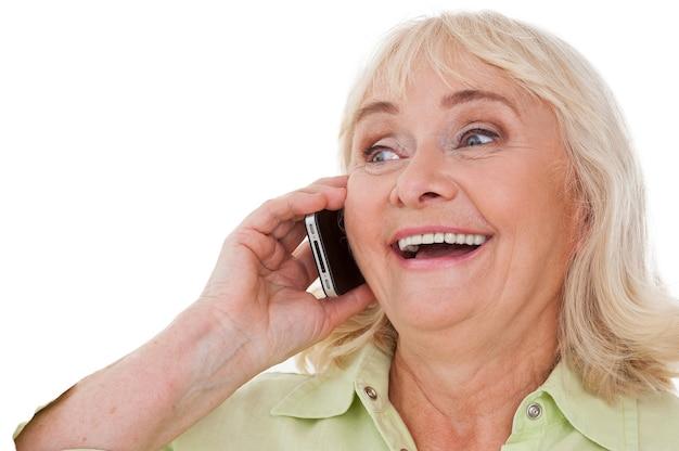 Boas notícias! mulher sênior feliz falando no celular e sorrindo em pé, isolado no fundo branco