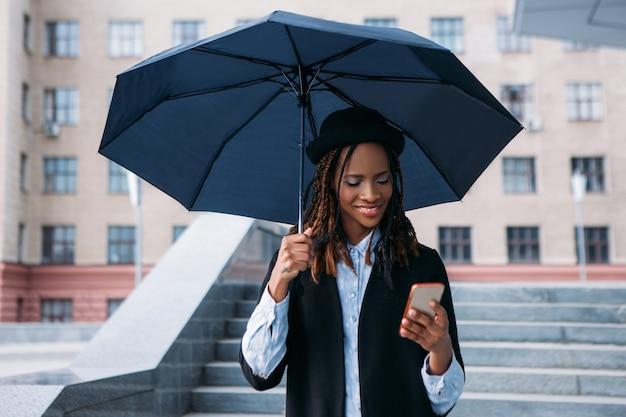 Boas notícias no celular. clima temperamental. mulher negra feliz com um guarda-chuva em dia chuvoso, moda de rua, conceito de felicidade