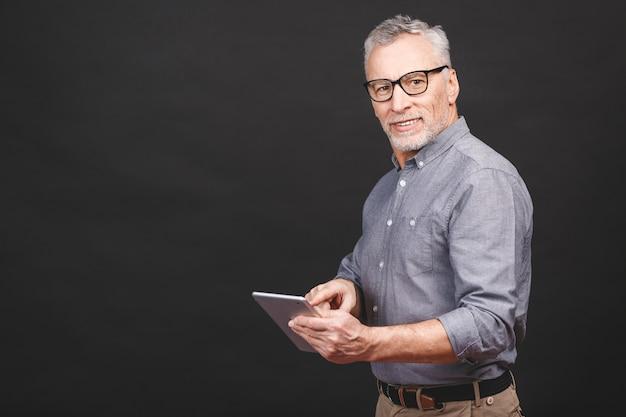 Boas notícias! o homem de negócios maduro considerável no vestuário desportivo esperto e nos óculos está usando uma tabuleta digital e sorrindo, olhando.