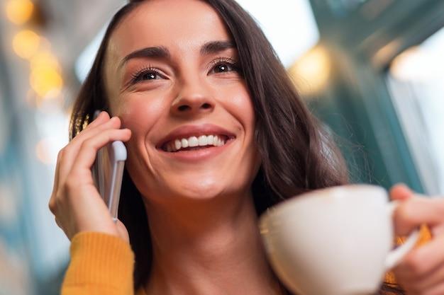 Boas notícias. perto de uma atraente mulher morena feliz segurando o telefone enquanto sorri e bebe chá