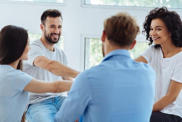 Boas pessoas positivas e encantadas sentadas em círculo e olhando umas para as outras, de mãos dadas