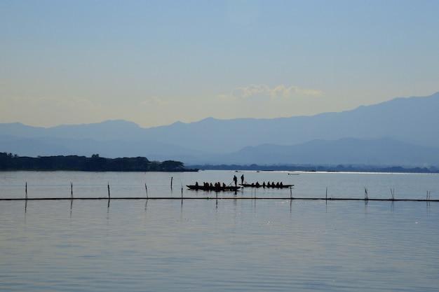 Boatman paddle para levar passageiros pelo vasto lago à noite em kwan phayao.
