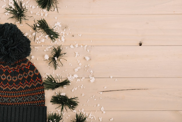 Bobble chapéu perto de neve e abeto agulhas