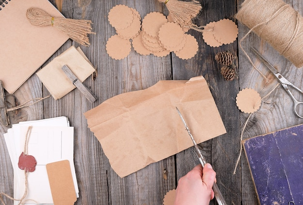 Bobina de corda marrom, etiquetas de papel e tesoura velha sobre uma superfície de madeira cinza