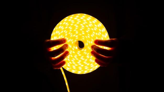 Bobina de faixa led brilhante com luz quente na mão.