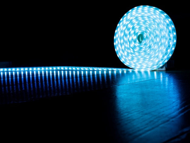 Bobina de faixa led para iluminação decorativa, faixa de diodo com luz fria azul sobre fundo escuro.
