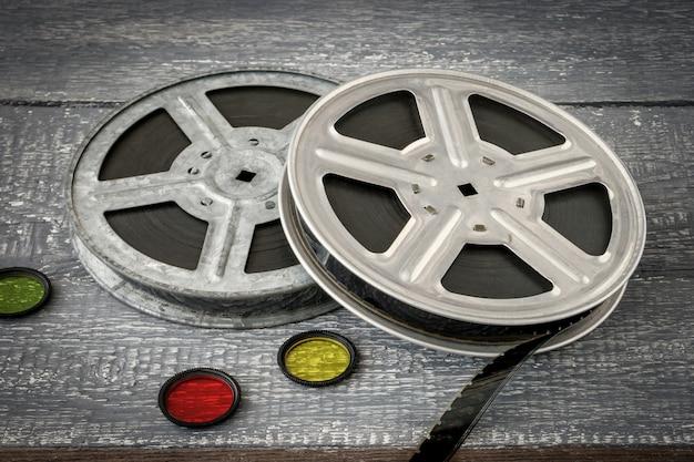 Bobinas com filmes antigos e filtros de vidro coloridos repousam sobre uma mesa de madeira