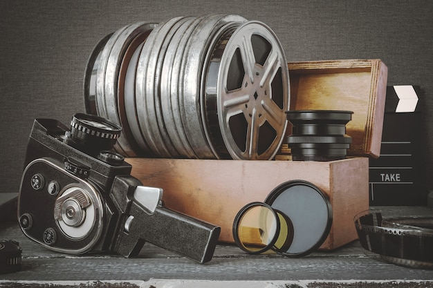 Bobinas com filmes em uma caixa de madeira, lente e uma câmera de filme antigo
