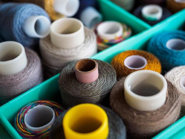 Bobinas com fios de cores diferentes para costura. tópicos localizados na caixa. a vista de cima nas linhas para costura.