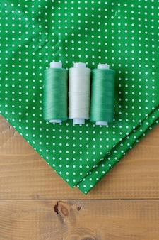 Bobinas com fios, fita métrica e pilha de tecidos coloridos na mesa.