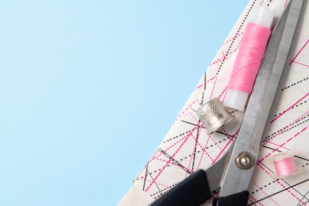 Bobinas de fio-de-rosa e padrão de tesoura e acessórios para bordado em azul