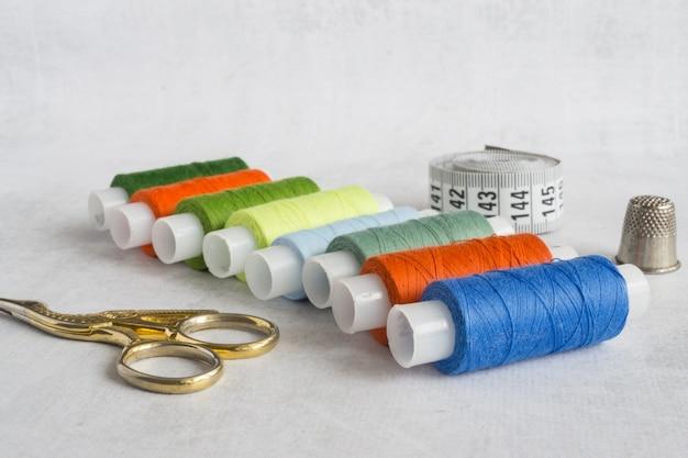 Bobinas de tesouras douradas com fios coloridos e fita métrica