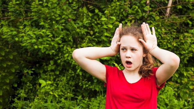 Boca aberta menina criança brincando com o gesto com a mão no parque olhando para longe