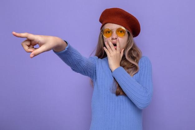 Boca coberta de medo com a mão apontando para o lado linda garotinha usando chapéu com óculos