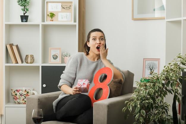 Boca coberta de surpresa com a mão bonita no dia da mulher feliz segurando um presente sentado na poltrona na sala de estar