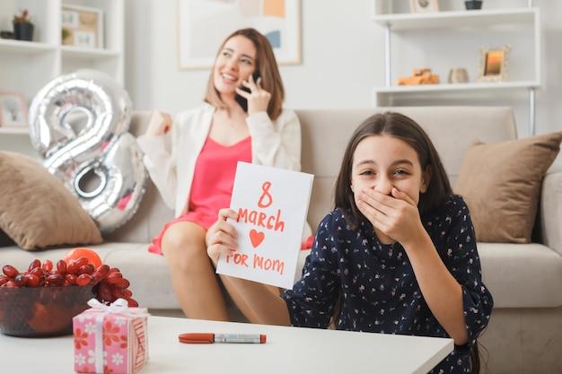 Boca coberta sorridente com a mão da filha segurando um cartão sentado no chão atrás da mesa de centro no dia da mulher feliz. a mãe sentada no sofá fala ao telefone na sala de estar