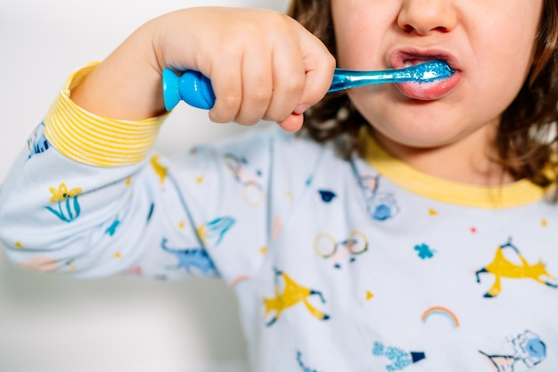 Boca de uma criança escovando os dentes com uma escova de dentes enquanto usava pijama antes de dormir