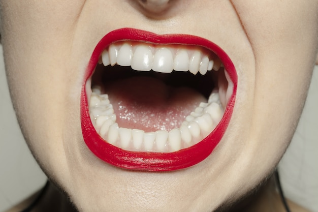 Boca feminina de close-up com maquiagem de lábios de brilho vermelho brilhante.