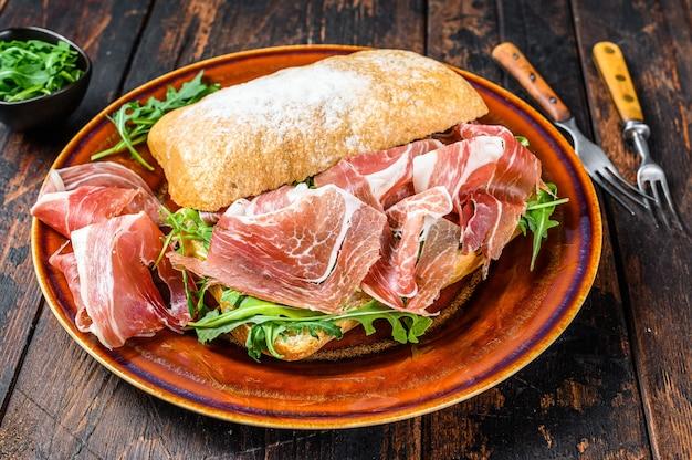 Bocadillo de jamon espanhol, sanduíche de presunto serrano no pão ciabatta com rúcula. fundo de madeira escuro. vista do topo.