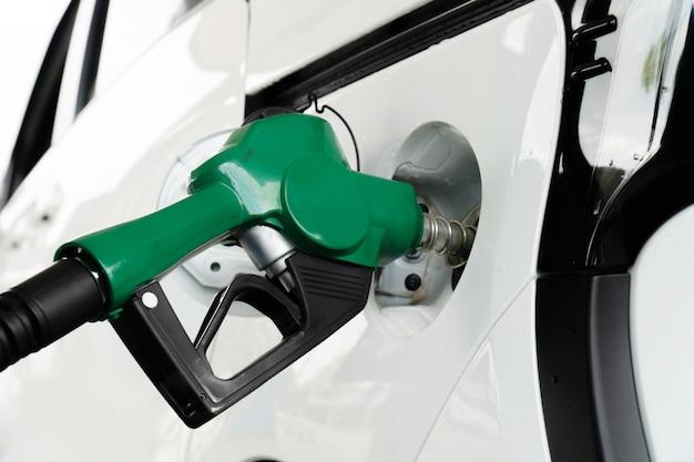 Bocal da bomba de gás no tanque de combustível de um carro branco.