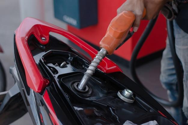 Bocal de combustível de mão em derramar a moto no posto de gasolina