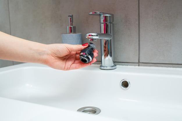 Bocal giratório no misturador para ajustar o fluxo de água. pia de banheiro branca para lavar as mãos