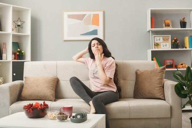 Bocejando com a boca coberta e uma jovem sentada no sofá atrás da mesa de centro na sala de estar