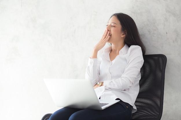 Bocejo asiático bonito da mulher do retrato em seu lugar de trabalho com laptop.