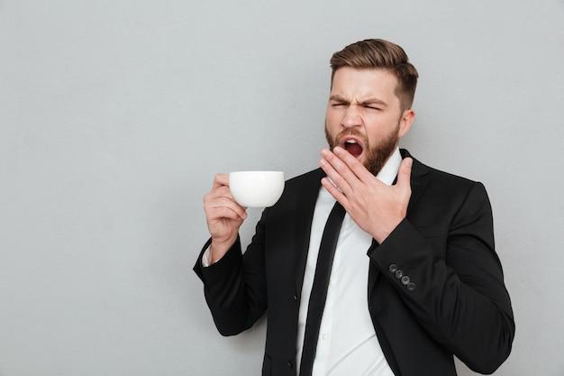 Bocejo barbudo homem de terno, bebendo café