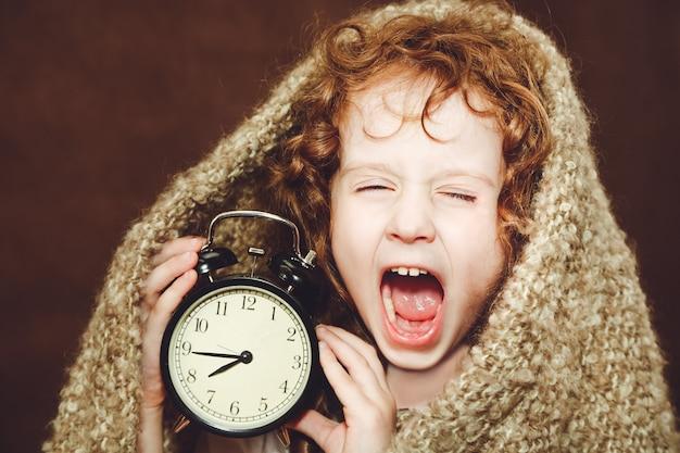 Bocejo da menina encaracolado e exploração despertador.