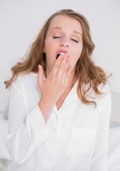 Bocejo mulher bonita sentada na cama dela
