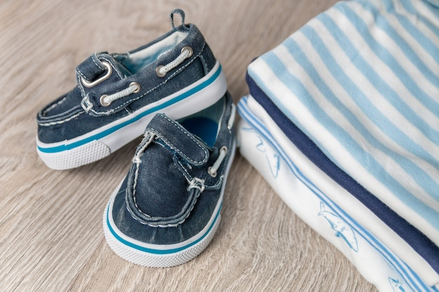 Body azul e branco dobrado com sapatos na fralda para menino recém-nascido. pilha de roupas infantis. roupa de criança. fechar-se.