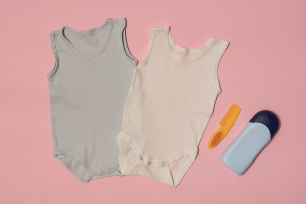 Body bebê azul e branco em um fundo rosa. acessórios. conceito de moda