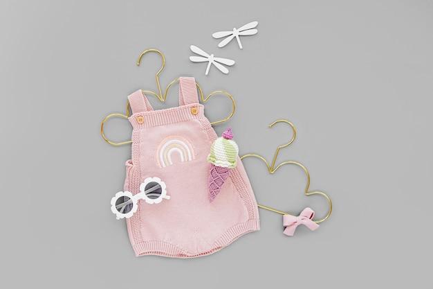 Body de malha rosa em cabide dourado com sorvete de brinquedo e óculos escuros. conjunto de roupas de bebê e acessórios para o verão. recém-nascido da moda. camada plana, vista superior