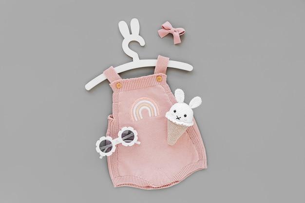 Body de malha rosa em cabide fofo com orelhas de coelho com sorvete de brinquedo e óculos escuros. conjunto de roupas de bebê e acessórios para o verão. recém-nascido da moda. camada plana, vista superior