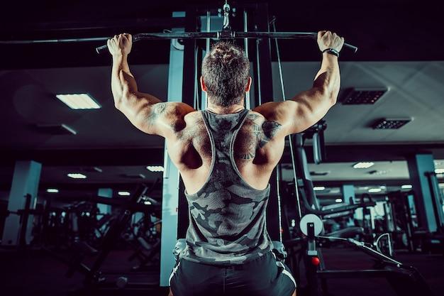 Bodybuilder forte que faz o exercício pesado para trás na máquina