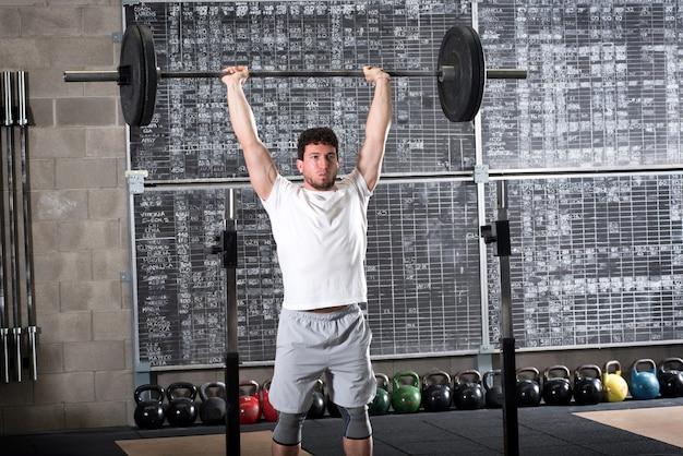 Bodybuilder forte que levanta barra pesada