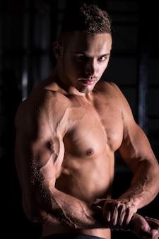 Bodybuilder jovem mostrando braço musculoso