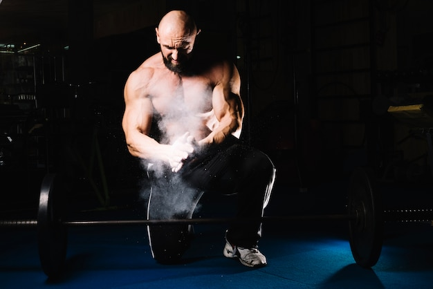 Bodybuilder masculino com barra
