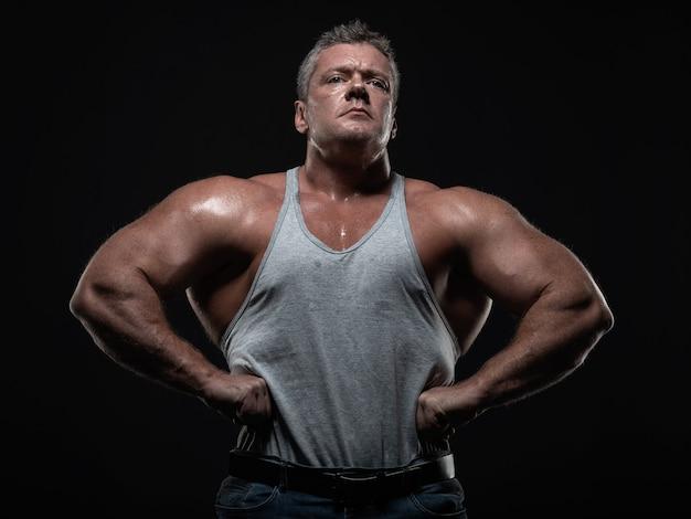 Bodybuilder muscular poderoso que levanta no preto. conceito de força e saúde