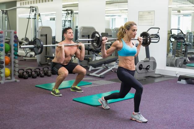 Bodybuilders levantando barras em conjunto no crossfit