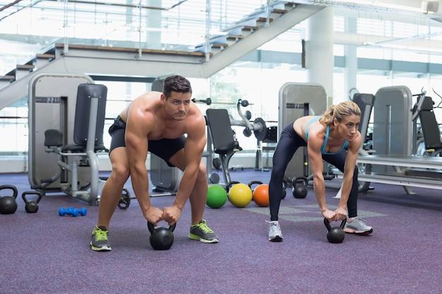 Bodybuilding homem e mulher levantando kettlebells em um agachamento